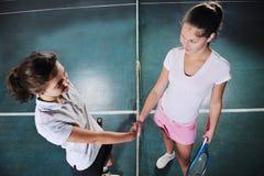 Młode dziewczyny bawić się tenisowy gemowy salowego obraz stock