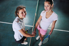 Młode dziewczyny bawić się tenisowy gemowy salowego zdjęcia stock