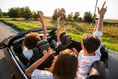 Młode dziewczyny i faceci siedzą w czarnym kabriolecie, trzymają ich ręki w górę i robią selfie na ciepłym słonecznym dniu, obraz royalty free