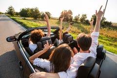 Młode dziewczyny i faceci siedzą w czarnym kabriolecie, trzymają ich ręki w górę i robią selfie na ciepłym słonecznym dniu, zdjęcie stock