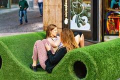 Młode dziewczyny relaksuje na ławce przy Genewa Obrazy Stock