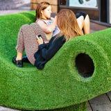 Młode dziewczyny relaksuje na ławce w Lemańskim mieście Obrazy Stock