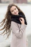 Młode dziewczyny rozwijają włosy w wiatrze Dziewczyna w czarnym żakiecie, szaliku i czerwonej sukni przeciw szaremu niebu, nie fotografia royalty free