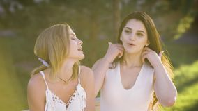 Młode dziewczyny w białych sukniach opowiadają each inny podczas spotkania w parku, kobiety siedzą na ławce zbiory
