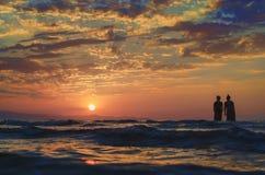 Młode dziewczyny w ciepłej wodzie przy zmierzchem Wspaniali kolory w niebie i morzu Ludzie stoi i ogląda zmierzch przy morzem kas obraz stock