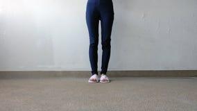 Młode Female's nogi, cieki Jest ubranym i Białego błękit i kapcie Dyszą na ziemi, Salowy tło Fotografia Royalty Free