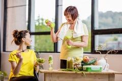 Młode i stare kobiety z zdrowym jedzeniem indoors fotografia stock