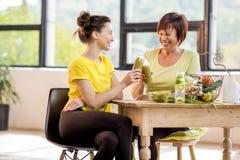 Młode i stare kobiety z zdrowym jedzeniem indoors zdjęcia royalty free