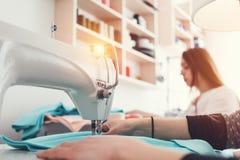Młode kobiet ręki i szwalna maszyna zakończenie Dwa młodych kobiet projektant odzieżowy działanie w kreatywnie studiu Zdjęcie Stock