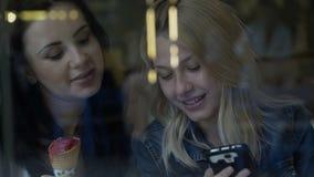 Młode kobiety śmia się nad wiadomością w ogólnospołecznych środkach karmią używać smartphone mienia lody w pub zdjęcie wideo