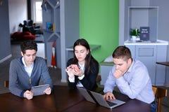 Młode kobiety i dwa mężczyzna przy lunchem są ruchliwie z ich swój sprawami Zdjęcia Royalty Free