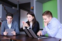 Młode kobiety i dwa mężczyzna przy lunchem są ruchliwie z ich swój sprawami Obrazy Stock