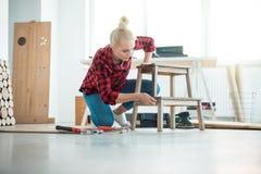 Młode kobiety naprawia meble w domu obrazy stock