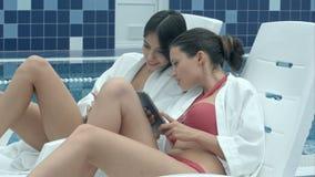 Młode kobiety relaksuje na holów krzesłach używa telefon i pastylkę blisko basenu zbiory