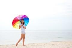 Młode kobiety skacze z parasolowym i szczęśliwym na plaży obrazy stock