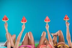 Młode kobiety trzyma arbuzów kawałki podczas gdy kłamający na pływackiej materac Obrazy Royalty Free