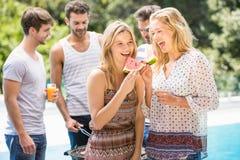 Młode kobiety uśmiecha się plasterek wodny melon i ma zdjęcia royalty free