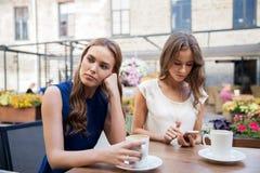 Młode kobiety z smartphone i kawą przy kawiarnią Zdjęcie Royalty Free