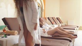 Młode kobiety z szkłem cieszy się jej wakacje przy zdroju kurortem sok pomarańczowy zbiory