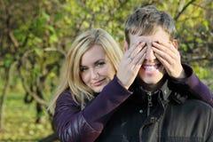 Młode kobiety zakrywający oczy uśmiechnięty mężczyzna rękami zdjęcia royalty free