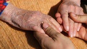 Młode męskie ręki pociesza starszą parę ręki babci plenerowy zakończenie up Zdjęcia Stock