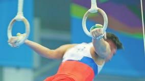 Młode mięśniowe gimnastyczki wykonuje elementy z gimnastycznymi pierścionkami zbiory