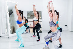 Młode nikłe kobiety robi koszt stały kucnięciu ćwiczą podczas grupowego szkolenia w gym zdjęcie stock