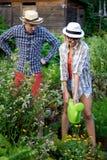 Młode ogrodniczki mężczyzna i kobieta w ogródzie Ona podlewanie kwiaty zdjęcie royalty free