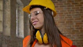 Młode piękne atrakcyjne kobiety w hełmie, słuchawki i, mruganie, żeński budowniczy, cegła zbiory wideo