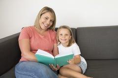 Młode piękne i szczęśliwe kobiety siedzi wraz z jej uroczej 7 lat uroczej blond dziewczyny czytelniczą książką cieszy się mówjący Fotografia Royalty Free