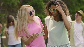 Młode piękne kobiety przegląda fotografie na smartphone w parku, przyjęcie, relaksują zbiory