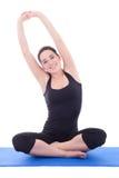 Młode piękne kobiety rozciągania ręki na joga macie odizolowywającej na w zdjęcia stock