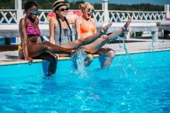 Młode piękne wieloetniczne kobiety siedzi blisko pływackiego basenu obrazy royalty free
