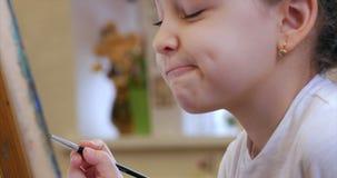 Młode ręki artysta, Mały kobieta artysta Malują kanwę z muśnięciem, Siedzący remis na kanwie i Ttable proces zbiory wideo