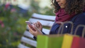 Młode shopaholic scrolling strony na smartphone, robić rozkazuje online, zakupy zbiory wideo