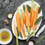 Młode soczyste marchewki, mędrzec, kwiecisty miód, czosnek, solankowi składniki dla wypiekowego karmelu korzennych marchewek Odgó fotografia royalty free