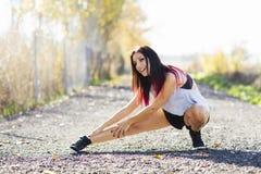 Młode sprawności fizycznej kobiety biegacza rozciągania nogi Przed bieg Obrazy Stock
