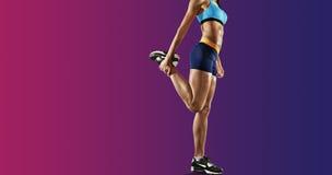 Młode sprawności fizycznej kobiety rozciągania nogi odosobniony fotografia royalty free