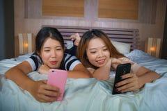 Młode szczęśliwe, ładne Azjatyckie Chińskie dziewczyny siedzi w domu sypialnię i mieć zabawę używać interneta socjalny zdjęcia royalty free