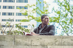 Młodego amerykanina afrykańskiego pochodzenia mężczyzna czytelnicza książka na górze ściany w Nowym Yo zdjęcia stock
