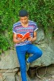 Młodego amerykanina afrykańskiego pochodzenia mężczyzna czytelnicza książka, podróżujący, relaksujący przy Obrazy Stock
