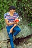 Młodego amerykanina afrykańskiego pochodzenia mężczyzna czytelnicza książka, podróżujący, relaksujący przy Obrazy Royalty Free