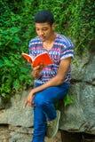 Młodego amerykanina afrykańskiego pochodzenia mężczyzna czytelnicza książka, podróżujący, relaksujący przy Zdjęcia Royalty Free