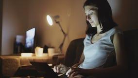 Młodego atrakcyjnego kobiety udzielenia ogólnospołeczni środki używać na laptopie w domu w nighttime zbiory