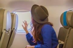 Młodego azjatykciego kobieta podróżnika przyglądający widok przy okno w samolocie z szczęściem i relaksować obraz stock