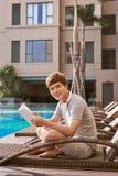 Młodego azjatykciego mężczyzna czytelnicza książka basenem na pogodnym letnim dniu obrazy stock