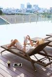Młodego azjatykciego mężczyzna czytelnicza książka basenem na pogodnym letnim dniu zdjęcia stock