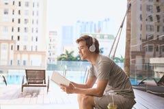 Młodego azjatykciego mężczyzna czytelnicza książka i słuchanie muzyka basenem zdjęcia royalty free
