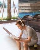 Młodego azjatykciego mężczyzna czytelnicza książka i słuchanie muzyka basenem fotografia royalty free