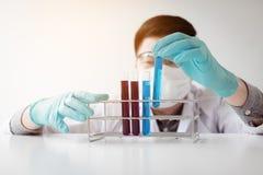 Młodego azjatykciego mężczyzna medycznego badacza próbnych tubk przyglądający szkło w l fotografia royalty free